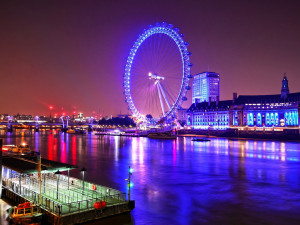 thames river with london eye ferris wheel in background at night
